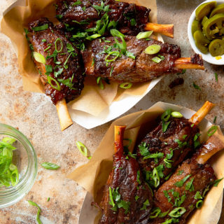 Two paper dishes full of three pig wings each surrounded by dishes of jalapeno, dip, and scallions.