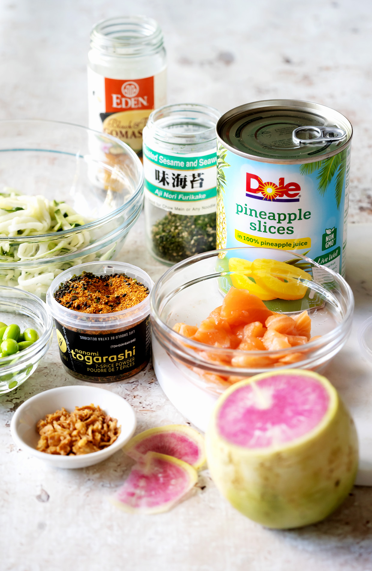 The ingredients for making a salmon bowl include, salmon, pineapple rings, zucchini noodels, edamame, Togarashi, Furikake, spicy mayo and ponzu sauce