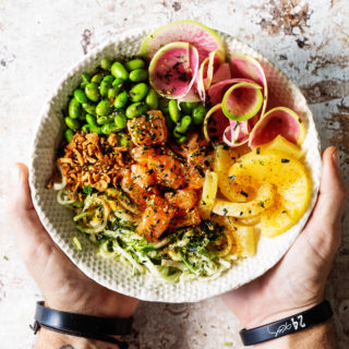 Salmon Poke Bowl with salmon, pineapple rings, radishes, edamame, and zucchini noodles.