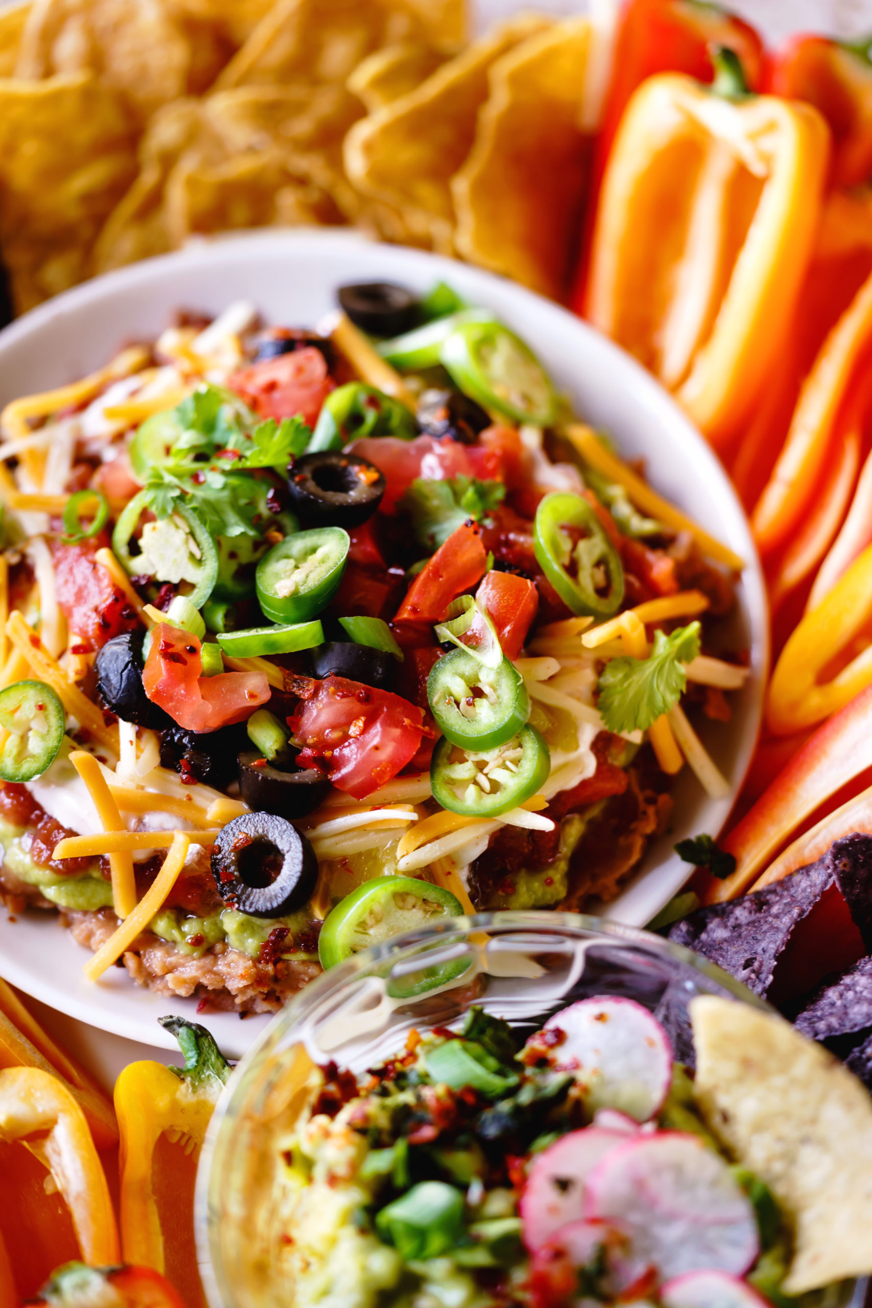 Seven-Layer Dip served with chips and crispy veggies.