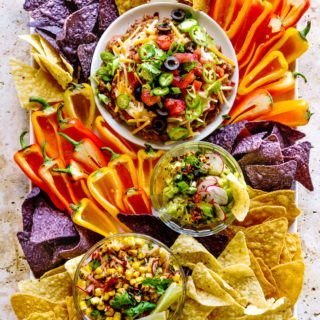 Summer Dip Board with a 7-Layer Bean Dip, Roasted Tomatillo Guacamole and Mexican Corn Dip.