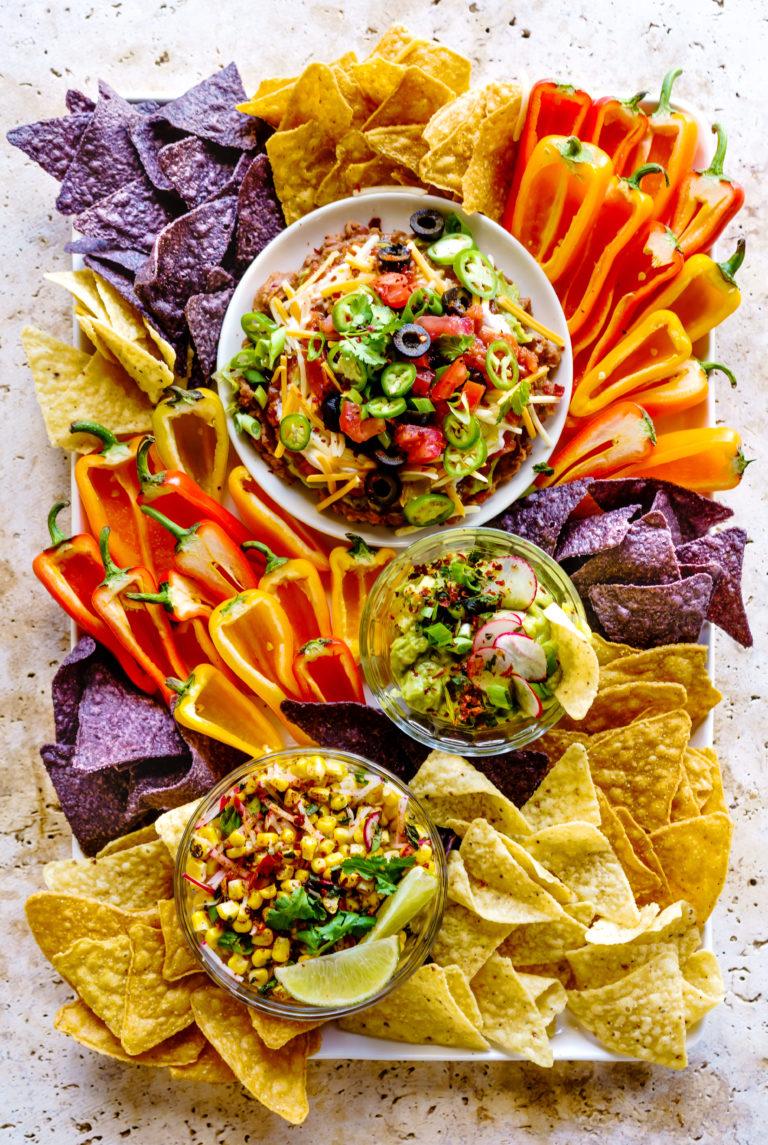 Summer Dip Board with a 7-Layer Bean Dip, Roasted Tomatillo Guacamole and Mexican Corn Dip.